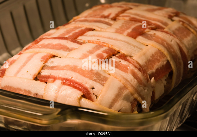 Uncooked Meatloaf wrapped with bacon in a basket weave pattern sitting in a clear Pyrex baking dish on a kitchen - Stock Image