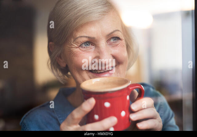 Senior woman at the window holding a cup of coffee - Stock Image