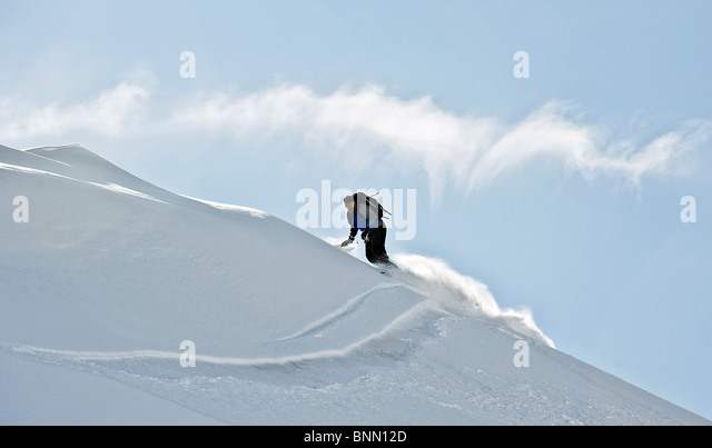 Snowboarder takes a powdery turn on a ridge in Hatcher Pass, Alaska - Stock Image