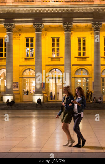 Young women texting with smartphone by the Grand Theatre in Place de la Comedie, Bordeaux, France - Stock Image