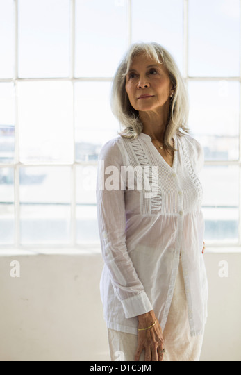 Portrait of senior woman in apartment - Stock Image