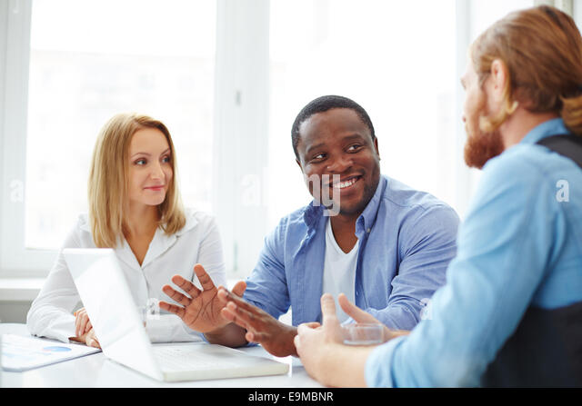 Group of co-workers in casual interacting at business meeting - Stock Image