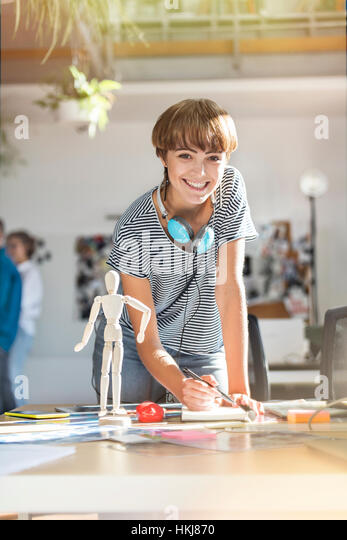 Portrait smiling female design professional with artist?s figure sketching in office - Stock-Bilder