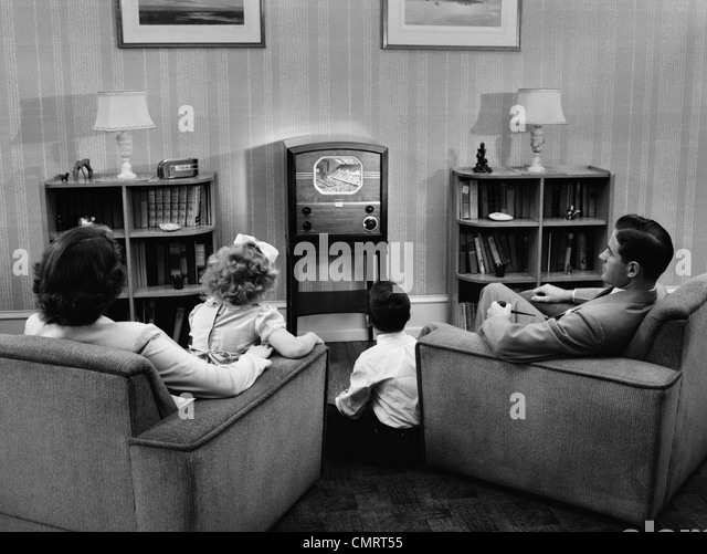 1940s 1950s FAMILY WATCHING TV IN LIVING ROOM - Stock Image
