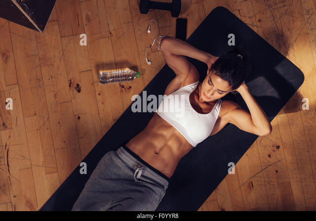 Sporty young woman lying on yoga mat doing sit-ups in gym. Top view of muscular woman doing abs crunches. - Stock-Bilder