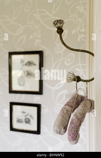 old fashioned padded hangers on ornate coat hook - Stock-Bilder