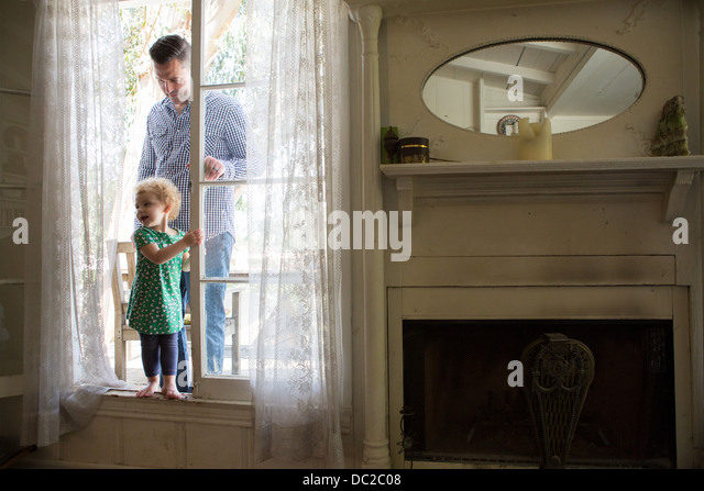 Father and child entering room from verandah - Stock Image