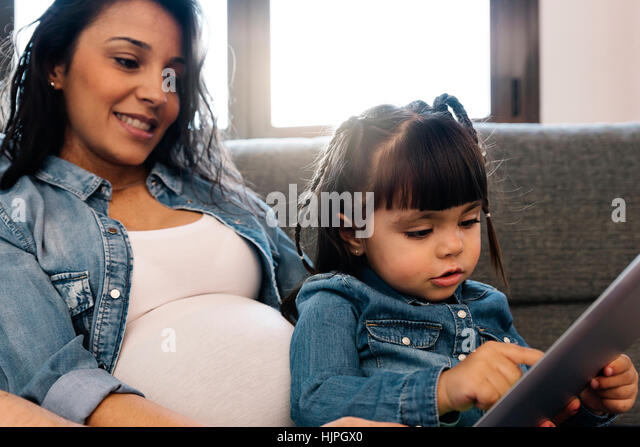 Happy family using tablet at home. - Stock Image
