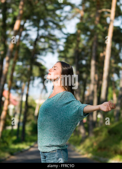 beautiful young woman enjoying the warm weather in an alley with green trees - Stock Image