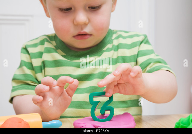 Little boy with modelling clay - Stock Image