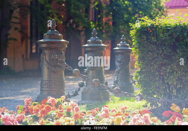 Decorative columns with lions and chains in Riga at the green lawn with flowers in sunny summer day - Stock Image