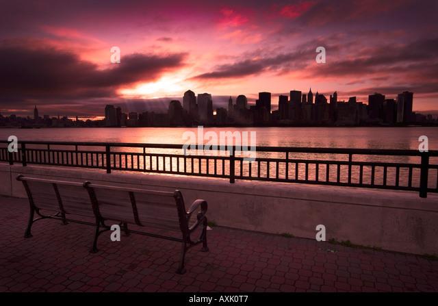 urban city sunrise sunset evening morning clouds sunlight water railing bench viewing sky pink orange white yellow - Stock Image