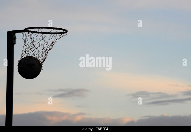 A Silhouette of a Netball going through a hoop with no players at dusk. - Stock Image