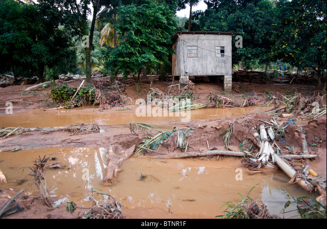 old shack still standing after a river overflows its banks during hurricane Tomas - Stock Image