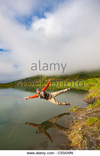 Humorous view of a fly fisherman falling into a lake with flyrod still in hand, Kenai Peninsula, Southcentral Alaska, - Stock Image