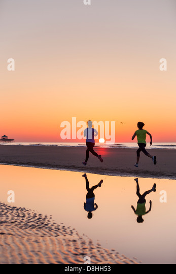 Two joggers running at beach - Stock Image