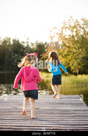 2 sisters running on  lake dock - Stock Image