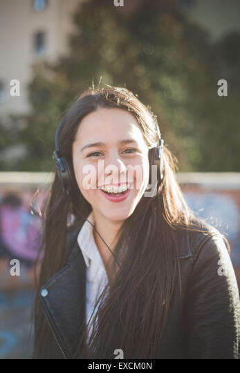 young beautiful long hair woman in town during sunset backlight listening music with headphones - Stock Image