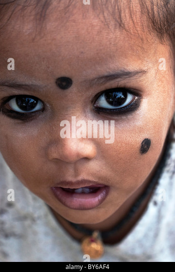 Small Indian child with kohl applied in spots to ward off 'the evil eye', South India. Kohl is an ancient - Stock Image