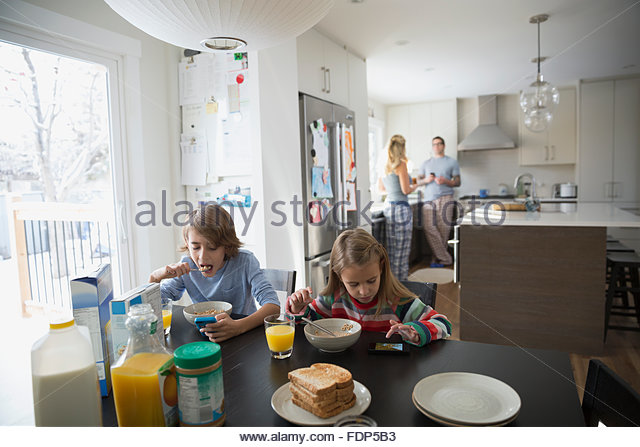 Family in kitchen and eating breakfast - Stock Image