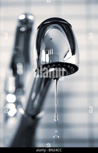 Water dripping from stainless steel kitchen faucet - Stock Image