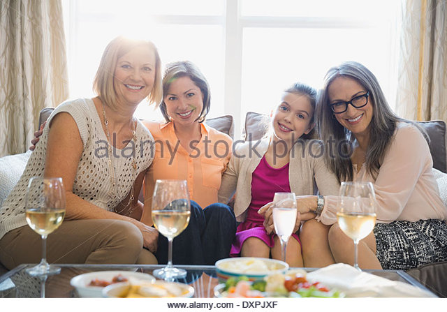 Portrait of smiling females sitting on sofa during party - Stock Image