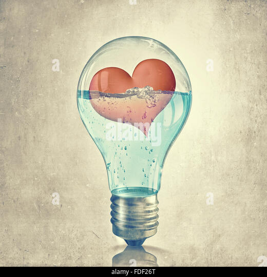 Glowing light bulb and red heart inside of it - Stock Image