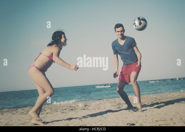 Couple playing volleyball on the beach - Stock Image