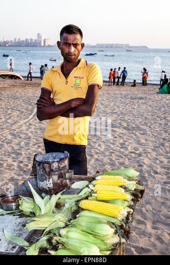 Mumbai India Asian Girgaon Marine Drive Chowpatty Beach public vendor roasted corn on cob man Arabian Sea - Stock Image