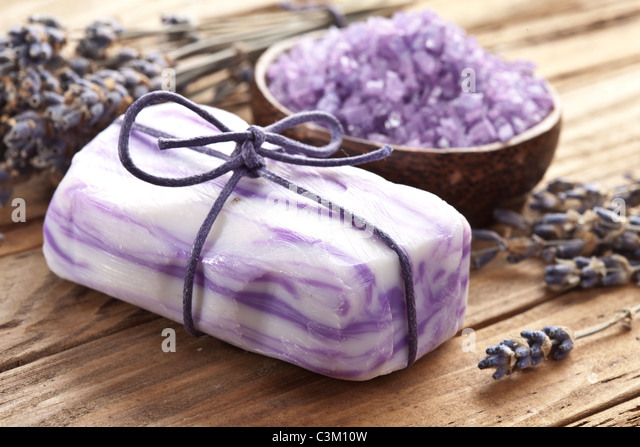 Soap with sea-salt and dried lavender on wood desk. - Stock Image