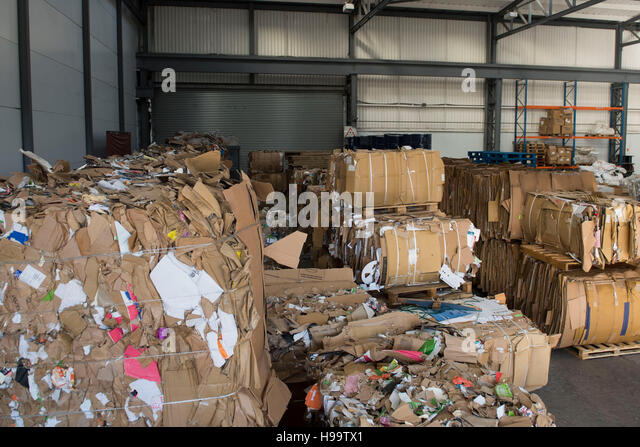 Piles of used cardboard ready for recycling in a factory. - Stock Image