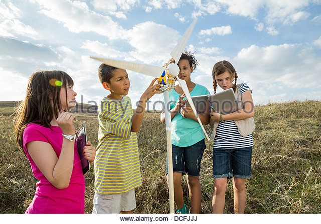 Schoolchildren using digital tablets while studying a wind turbine model - Stock Image