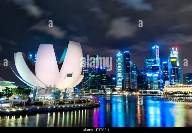 The Singapore skyline at night with the ArtScience museum in the foreground. - Stock Image