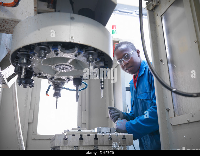 Apprentice engineer using CNC (computer numerical controlled) lathe in factory, portrait - Stock Image