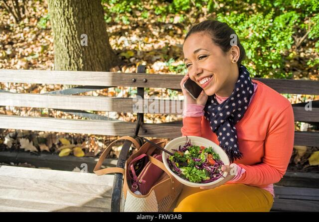 Young woman sitting on park bench chatting on smartphone whilst eating lunch - Stock Image
