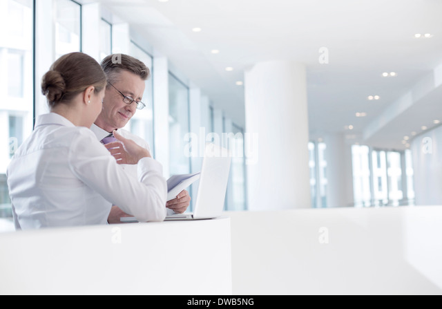 Business people working at railing in office - Stock Image