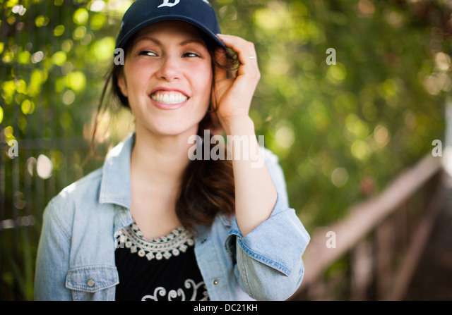 Mid adult woman wearing cap and smiling - Stock Image
