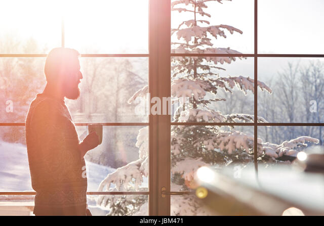 Man drinking coffee at sunny window with view of snowy trees - Stock-Bilder