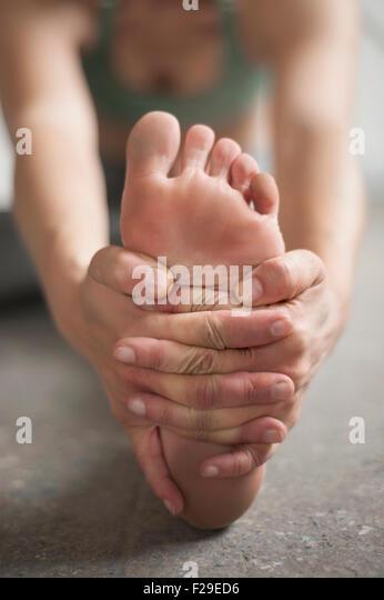 Woman practicing janu sirsasana pose in yoga studio, Munich, Bavaria, Germany - Stock Image