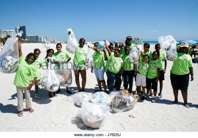 Miami Beach Florida Honey Shine Green Day Black girl student teen volunteer clean-up collected trash litter pollution - Stock Image