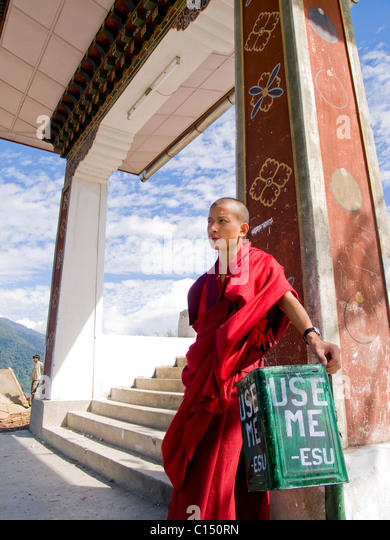 Buddhist monk leaning against a trash bin - Stock Image