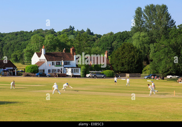 Local teams playing a cricket match on village green in front of Barley Mow pub on a summer's evening. Tilford - Stock Image