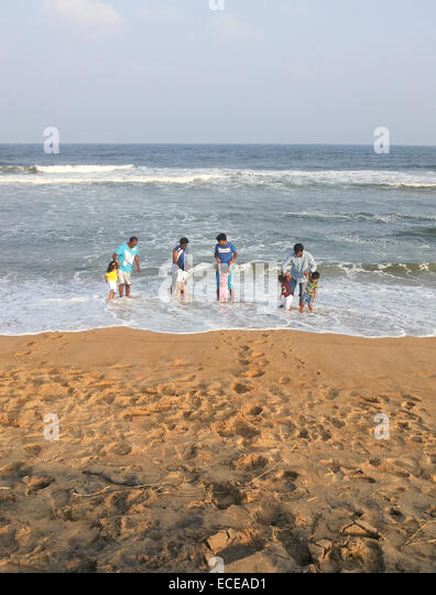 India, Fathers and children (2-7) playing on beach - Stock Image