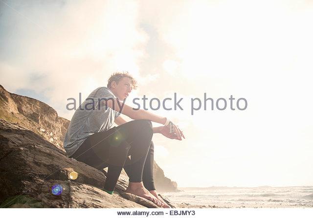 Teenage boy sitting on rocks - Stock Image