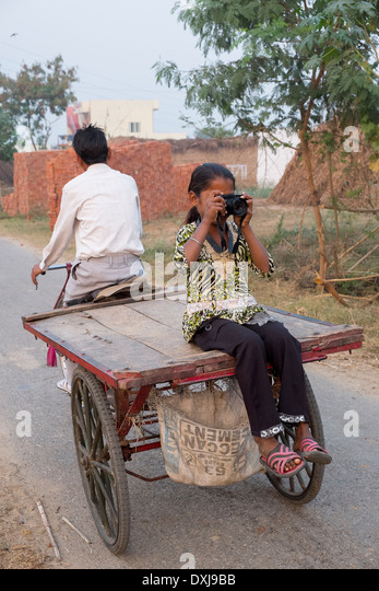 India, Uttar Pradesh, Agra, young girl riding on the back of a bicycle trailer using modern digital camera - Stock-Bilder
