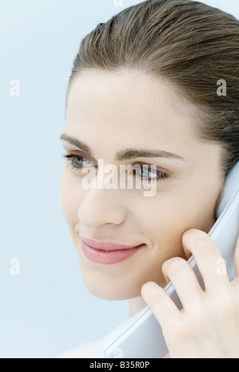 Young woman holding landline phone, looking away, cropped portrait - Stock-Bilder