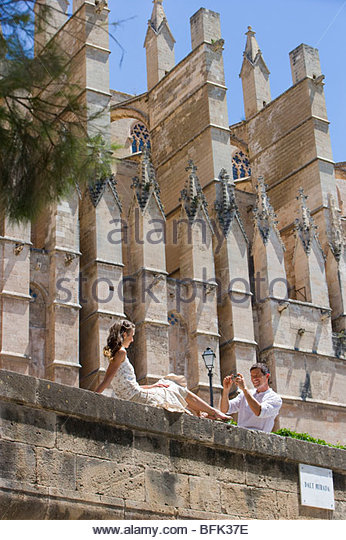 Man photographing woman on ledge - Stock Image