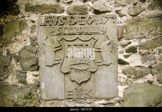 Medieval carved stone shield tablet displayed in small museum at St. Patrick's Rock of Cashel medieval complex - Stock Image