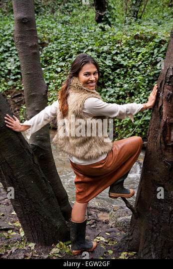 Woman standing in middle of tree. - Stock Image