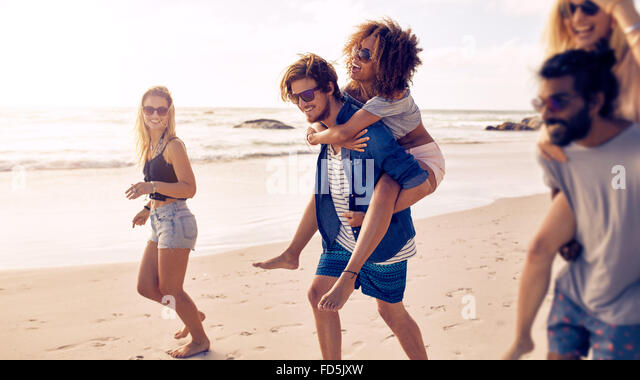 Two happy young men giving their girlfriends piggyback rides at the beach. Group of friends enjoying beach holidays. - Stock-Bilder